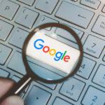 lupa powiększająca, pod którą widać świecący, biały guzik, z kolorowym napisem Google. Reszta klawiszy na klawiaturze jest bez zmian, w białym kolorze.