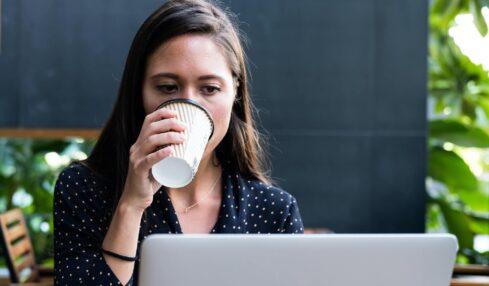 kobieta z kawą przy laptopie